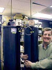 John Lloyd, K7JL, next to two of the four cavities making up this repeater's duplexer.
